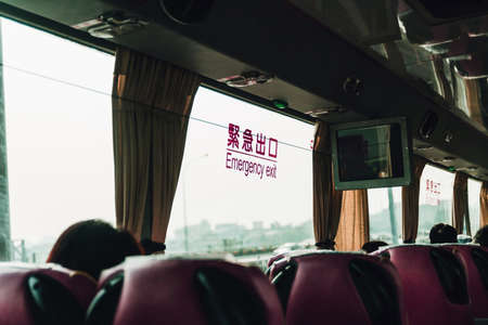Emergency Exit sticker in English and Chinese words stick on the window of the bus. Inside the bus that on the way to Yehliu, Taipei, Taiwan.