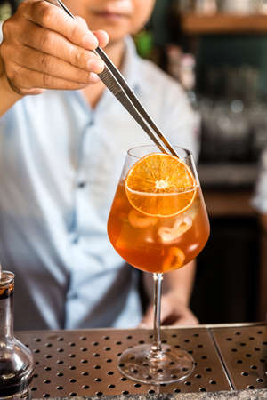 Mixologist decorates sliced orange on the orange fruity cocktail that mix with lychee in a wine glass. Banque d'images