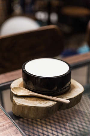 Japanese fusion dessert: White smooth milk pudding. Serve in a black ceramic bowl on timber with wooden spoon. Stock Photo
