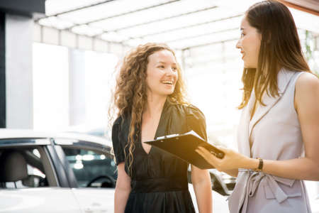 The Asian woman salesperson talking and explaining about insurance to a smiling and happy Caucasian woman client before hand over a new car. Automotive Leasing and Dealing Business.