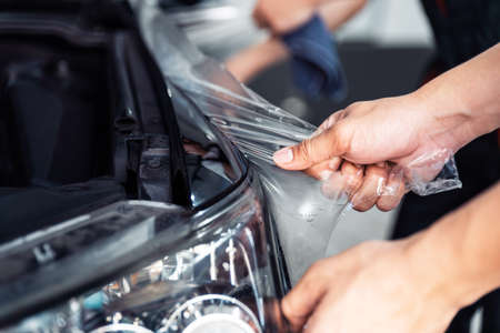 PPF installation process, close-up stretching removing an old transparent film on a car headlight and hood by hand. Automobile professional service.