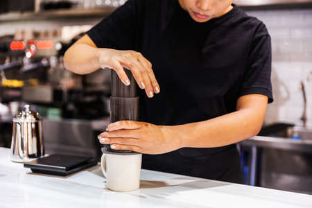 Aero press system coffee preparation method. Woman barista in a black T-shirt press Aeropress to fill a glass with espresso coffee on the marble counter. Professional coffee brewing cafe.