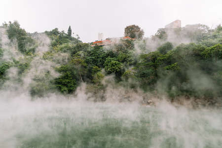 The famous Beitou Thermal Valley in Beitou Park, boiling steam from hot spring floating through the trees in Taipei City, Taiwan. Banco de Imagens