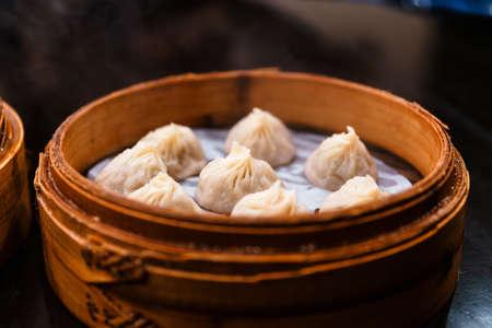 Steamed Xiao Long Bao (Soup Dumplings) in The Bamboo Basket. Served in Restaurant in Taipei, Taiwan. Фото со стока