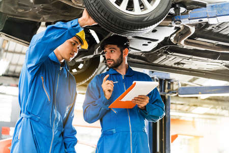 Mechanic in blue work wear uniform inspects the car bottom with his assistant. Automobile repairing service, Professional occupation teamwork. Vehicle maintenance.