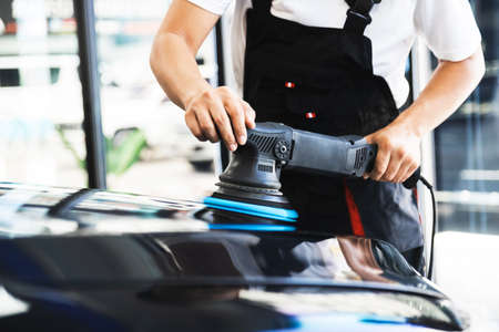 Crop image of professional car polishing rubs orbital polisher to polishing on the black car hood, remove scratch and restore a real shiny car paint. Automotive cleaning and coating service.