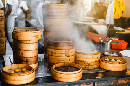 Piles of stacking bamboo steamers are steaming for dim sum in front of the restaurant with blur chefs in background in Taipei, Taiwan. Focus on front bamboo steamers. Reklamní fotografie