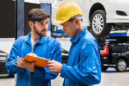 Mechanic in blue work wear uniform checks the vehicle maintenance checklist with his assistant with blur lifted car in the background. Automobile repairing service, Professional occupation teamwork.