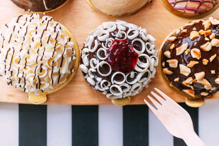 Many kinds of colorful Bavarian cream donuts contain chocolate, white chocolate, fruit jam, crush peanut, and more on a wooden plate with a wooden fork that ready to pick. Tasty and delicious desserts 免版税图像