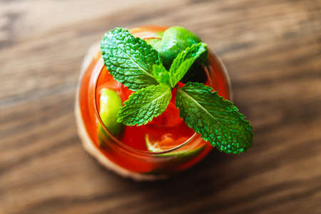 Red fruit cocktail mixed with sliced ​​lemon and topped with green fresh mint leaves. Sweet and sour drink combined with the intensity of the liquor and the cool smell of mint.
