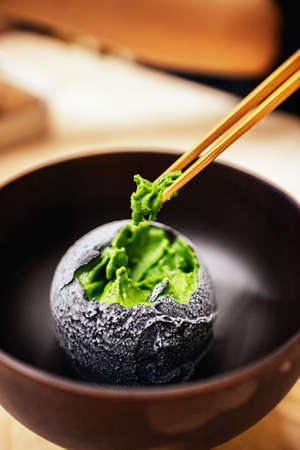 Charcoal coated a scoop of homemade green tea ice cream pinching with chopsticks in Japanese teahouse dessert cafe. Tasty exotic fusion dessert in Asian style.