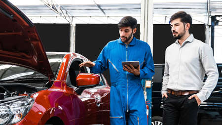 Mechanic man shows report on a digital tablet to the Middle East client at garage, A man mechanic and client discussing repairs done to his vehicle. Changing automobile business.