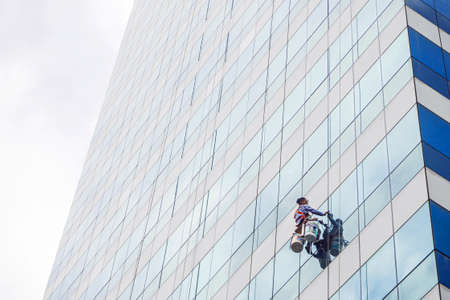 The worker cleaning glass window at the high rise building with the hanging rope climber. Glass windows building cleaning service. Risky service. Special Job concept.