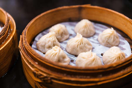 Steamed Xiao Long Bao (Soup Dumplings) in The Bamboo Basket. Served in Restaurant in Taipei, Taiwan. Archivio Fotografico