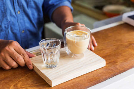 Male barista serve hot latte coffee and fresh water in drinking glass at the wooden counter bar. Served on wooden plate. 免版税图像
