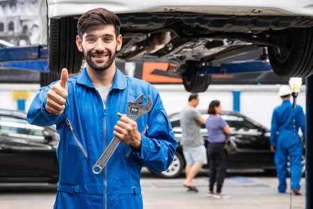 Mechanic thumb up standing and hold a wrench with blur garage in the background. Auto car repair service center. Professional service.