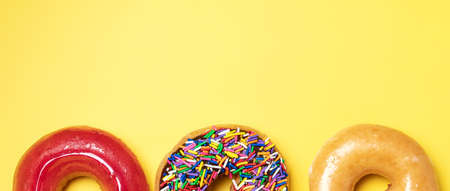 Top view of chocolate frosted donut with sprinkles, sugar-glazed frosted and strawberry glazed donut on yellow background. Playful and joyful tasty sugary comfort food with copy space.