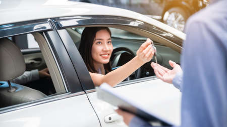 Car Dealership. The Asian woman receiving a car key with a smile form the salesman before hand over. Auto Leasing Business. Automotive Leasing and Dealing Business. International Business. 免版税图像