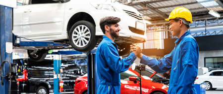 Mechanic in blue work wear uniform, shake hands with his assistant with a lifted car in the background. Automobile repairing service, Professional occupation teamwork. Vehicle maintenance.