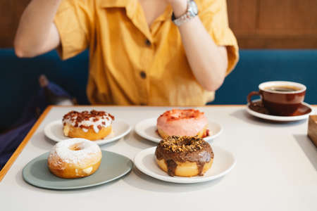 Woman wearing yellow shirt taking photos of strawberry pink, chocolate, sugar glazed and bacon, cheese donut with feeling happy a modern cafe. Enjoyment female lifestyle. 免版税图像
