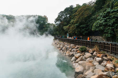 Tourist travel in the famous Beitou Thermal Valley in Beitou Park, boiling steam from hot spring floating through the trees in Taipei City, Taiwan.
