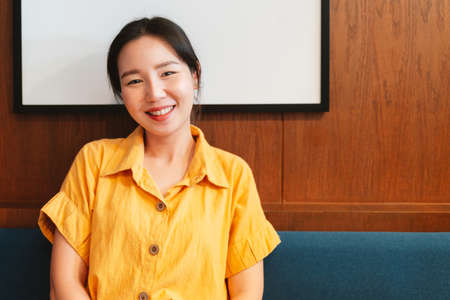 Happy smiling Asian woman wearing a yellow shirt and sitting in the modern cafe. Enjoyment of the female lifestyle.