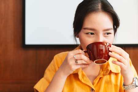 A pretty Asian woman wearing a yellow shirt is drinking coffee in the cafe with happy eyes. Enjoyment female lifestyle. Focus on a coffee cup.