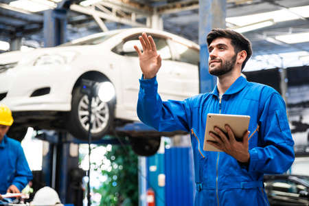Mechanic in blue workwear uniform holding tablet and check something with blur lifted car in the background. Automobile repairing service, Professional occupation teamwork. Vehicle maintenance.