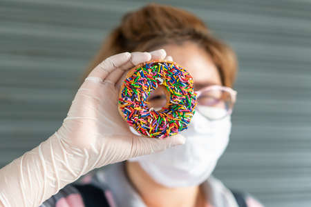 Woman baker wearing latex gloves, holding a fresh chocolate frosted donut and looking at the hole of the donut. Playful and joyful tasty sugary comfort food for customers. 免版税图像
