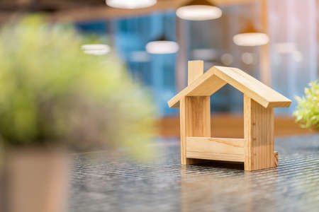 Miniature wooden houses and blur green plants in the foreground. Buying the first dream house with a young family. Affordable and Eco housing business. Residential and Real Estate development.
