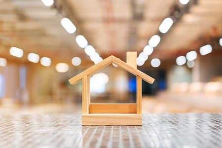 Miniature wooden houses and blur light in the background. Buying the first dream house with a young family. Affordable and Eco housing business. Residential and Real Estate development.