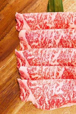 Premium Rare Slices Wagyu A5 beef with high-marbled texture on square wooden plate served for Sukiyaki and Shabu. Stok Fotoğraf