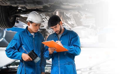 Mechanic in blue workwear uniform checks the vehicle maintenance checklist with his assistant under the lifted car. Automobile repairing service, Professional occupation teamwork. Vehicle maintenance. Stok Fotoğraf