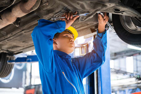 Asian mechanic wearing blue workwear and safety helmet examining the car bottom with wrenches. Auto car repair service center. Professional service.