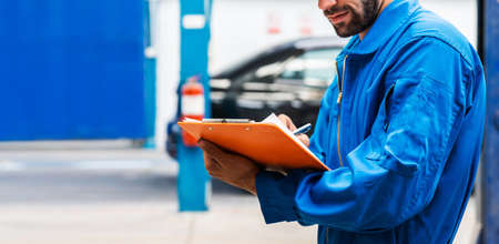 Crop image of mechanic in blue work wear uniform checks the vehicle maintenance checklist with blur lifted car in the background. Automobile repairing service, Professional occupation. Stok Fotoğraf
