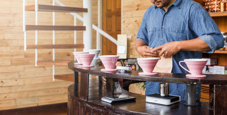 Male Barista making pour-over coffee with alternative method called Dripping. Coffee grinder, coffee stand and pour-over on a wooden counter.