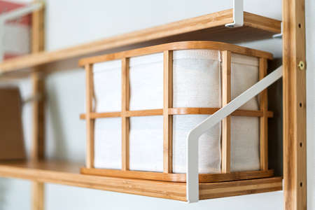 Canvas fabric storage basket with a wooden frame on the shelf. Eco-Friendly design product for home decoration. Sustainability lifestyle.