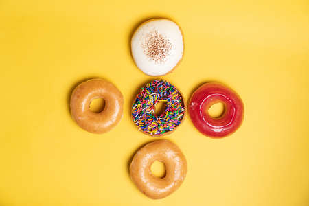 Top view of a chocolate frosted donut with sprinkles, sugar-glazed frosted, strawberry glazed and Bavarian donut on yellow background. Playful, creative and joyful tasty sugary comfort food. Stok Fotoğraf