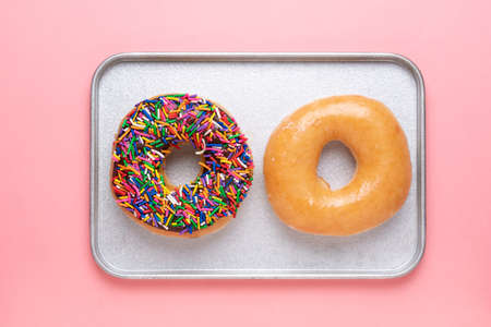 Top view of chocolate frosted donut with sprinkles and sugar-glazed frosted donut on baked plate. Playful and joyful tasty sugary comfort food for customers.