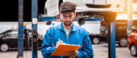 Mechanic in blue work wear uniform checks the vehicle maintenance checklist with blur lifted car in the background. Automobile repairing service, Professional occupation.