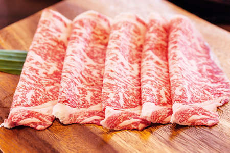 Crop image of Premium Rare Slices Wagyu A5 beef with high-marbled texture on square wooden plate served for Sukiyaki and Shabu.