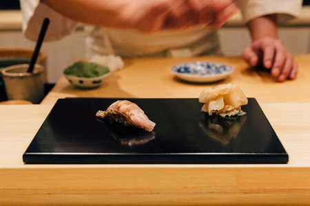 Japanese Omakase meal: Yellowtail Amberjack Sushi served by hand with pickled ginger on glossy black plate. Japanese traditional and luxury meal.