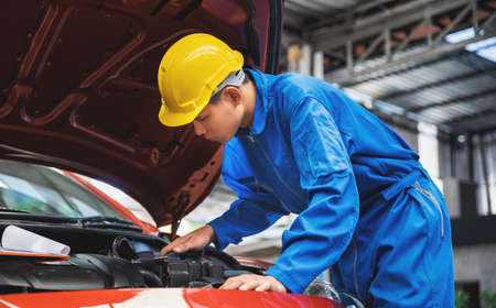 Asian mechanic wearing a safety helmet, checking the car engine in an opened hood car. Auto car repair service center. Professional service.