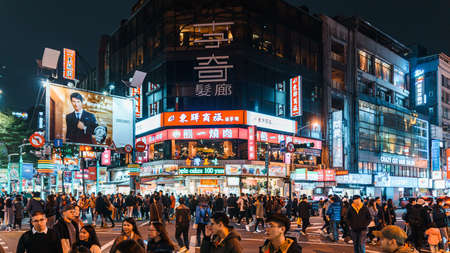 Decorated Colorful lights on buildings and advertisement boards with traffic and people walking on crosswalk in the night at Ximending in Taiwan, Taipei. 版權商用圖片