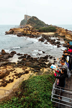 NEW TAIPEI CITY, TAIWAN. DEC 30, 2017: Aerial view diversity of tourists walking in Yehliu Geopark, a cape on the north coast of Taiwan. A landscape of honeycomb and mushroom rocks eroded by the sea. 新聞圖片