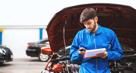 Mechanic in blue workwear uniform checks the vehicle maintenance checklist in a smartphone while sitting in the front hood in the garage. Automobile repairing service, Professional occupation.