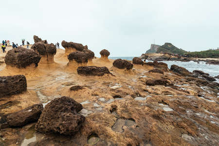 NEW TAIPEI CITY, TAIWAN. DEC 30, 2017: Diversity of tourists walking in Yehliu Geopark, a cape on the north coast of Taiwan. A landscape of honeycomb and mushroom rocks eroded by the sea. 新聞圖片