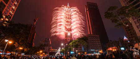 TAPEI, TAIWAN. JAN 1, 2018: Taipei City Night landscape and Taipei 101 skyscraper is lit up by fireworks. People watching and taking photos and videos around buildings to celebrate the new year event.
