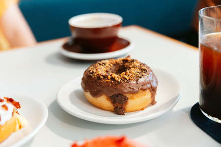 Donuts on the table, A chocolate glazed homemade donut topping with crush hazelnut. Enjoyment female lifestyle.