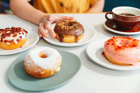 Donuts on the table include Strawberry pink, chocolate, sugar glazed and bacon, cheese donut on the table with the woman wearing yellow shirt in background in modern cafe. Enjoyment female lifestyle.